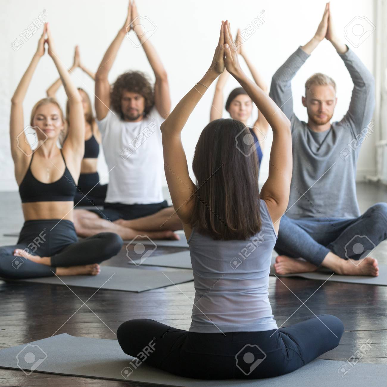 Group Of Young Sporty People Practicing Yoga Lesson With Instructor Sitting In Sukhasana Exercise