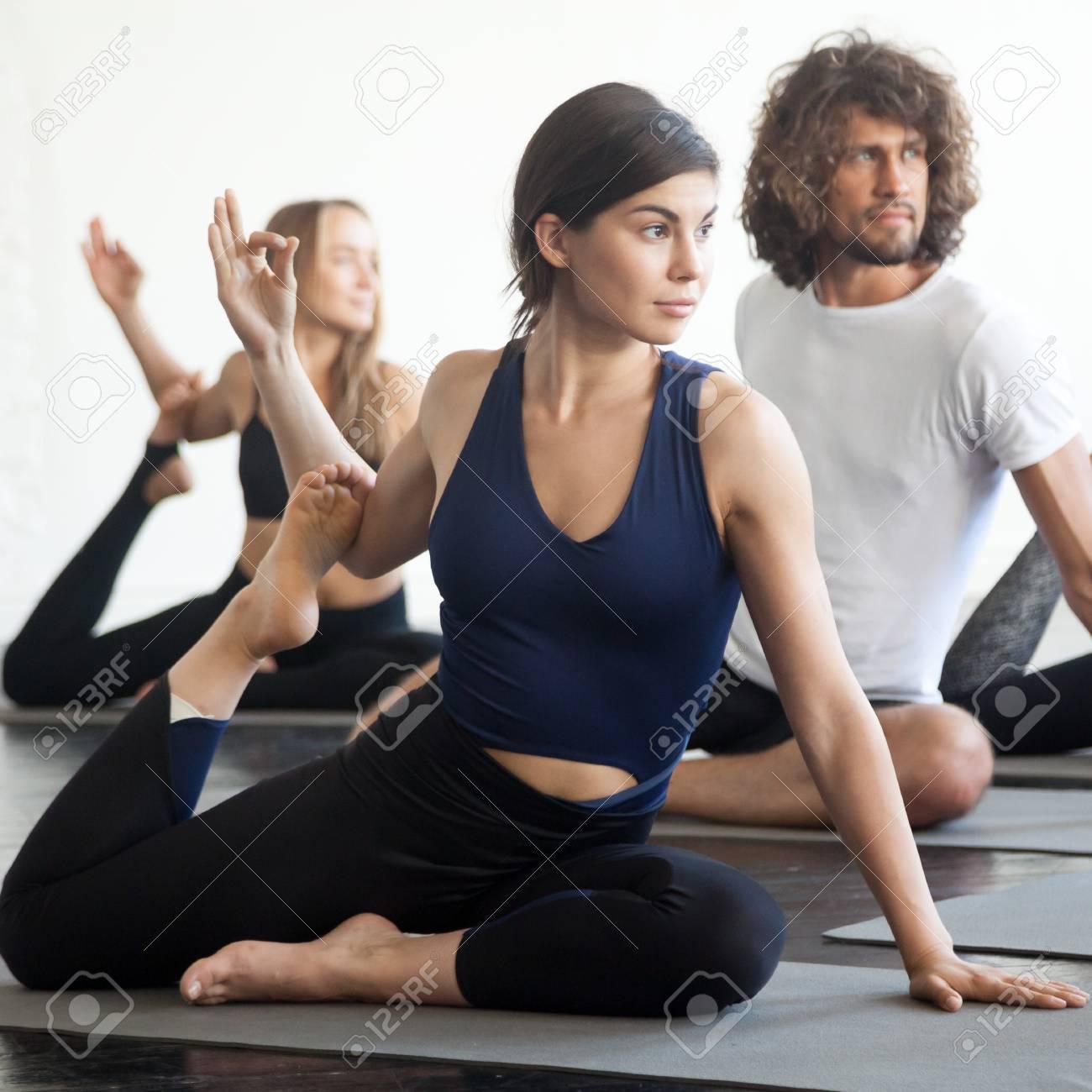 Grupo de jóvenes deportistas atractivas mujeres y hombres estudiantes trabajando, practicando la lección de yoga con instructor, sentado en el