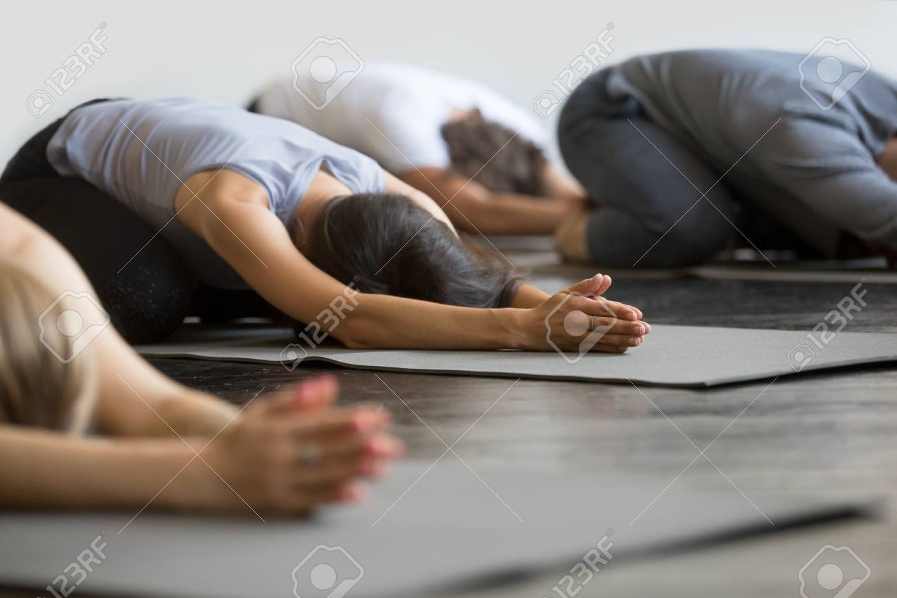 Group of young sporty people practicing yoga lesson with instructor, sitting in Balasana exercise, Child pose, friends working out in club, indoor close up image, studio. Wellbeing, wellness concept - 87651220