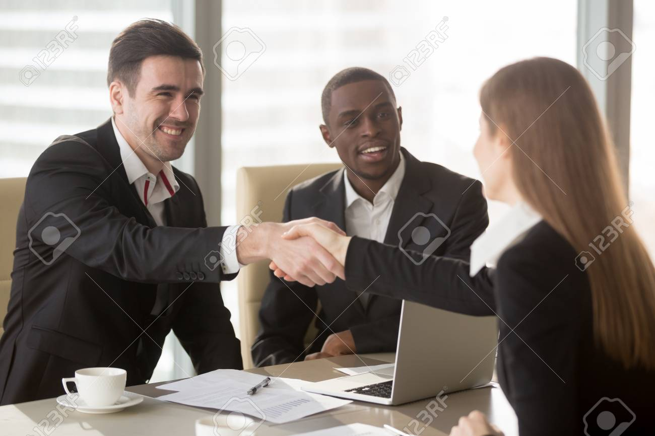 Happy smiling caucasian and afro american businessmen handshaking happy smiling caucasian and afro american businessmen handshaking with female job applicant or businesswoman on meeting m4hsunfo