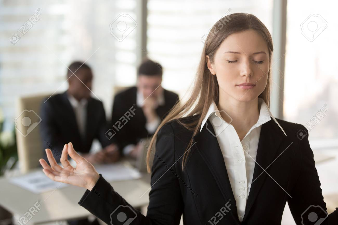 portrait of attractive female office worker trying to keep calm in difficult situation at work