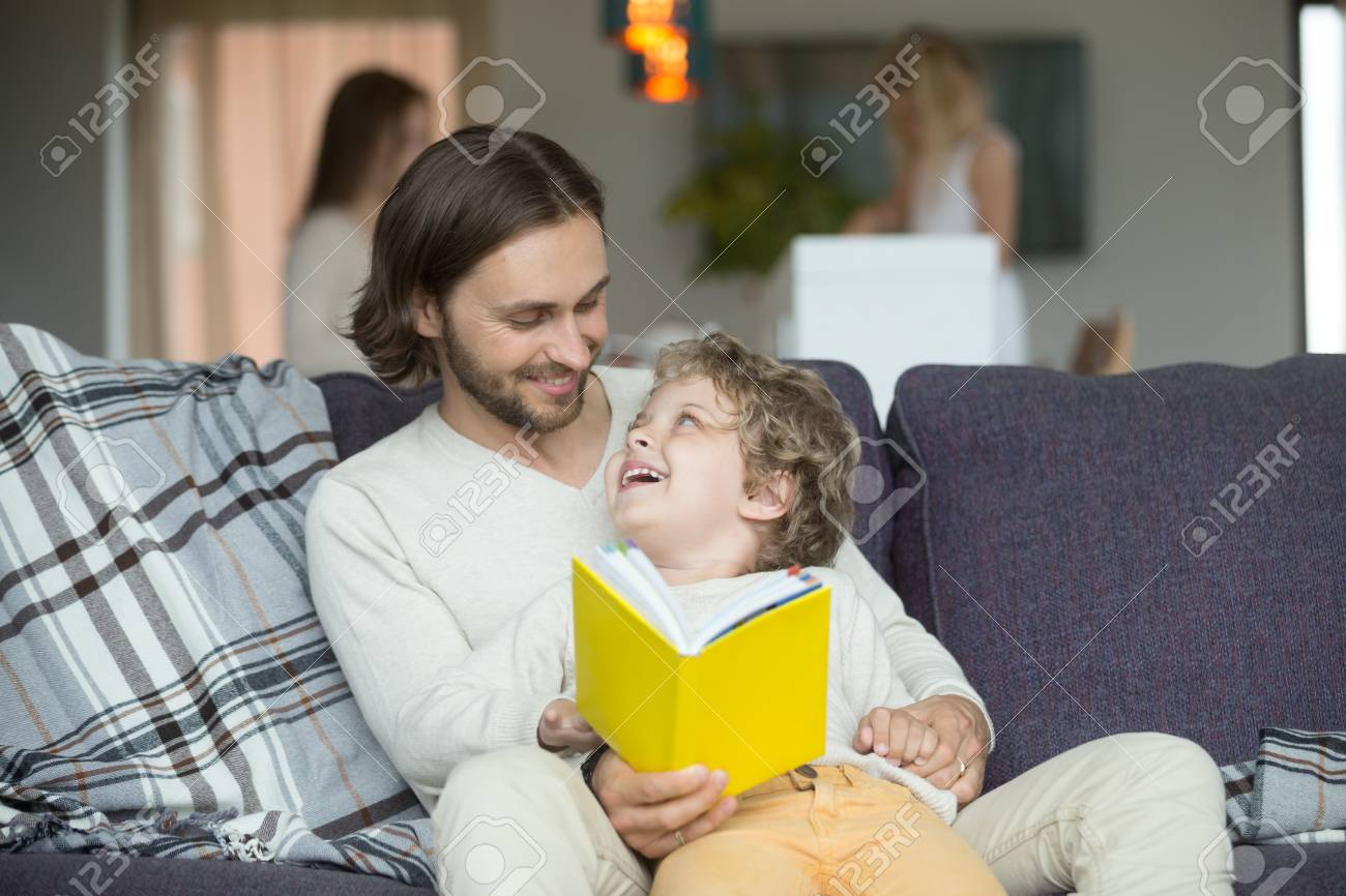Happy father and son holding yellow book sitting on sofa, dad