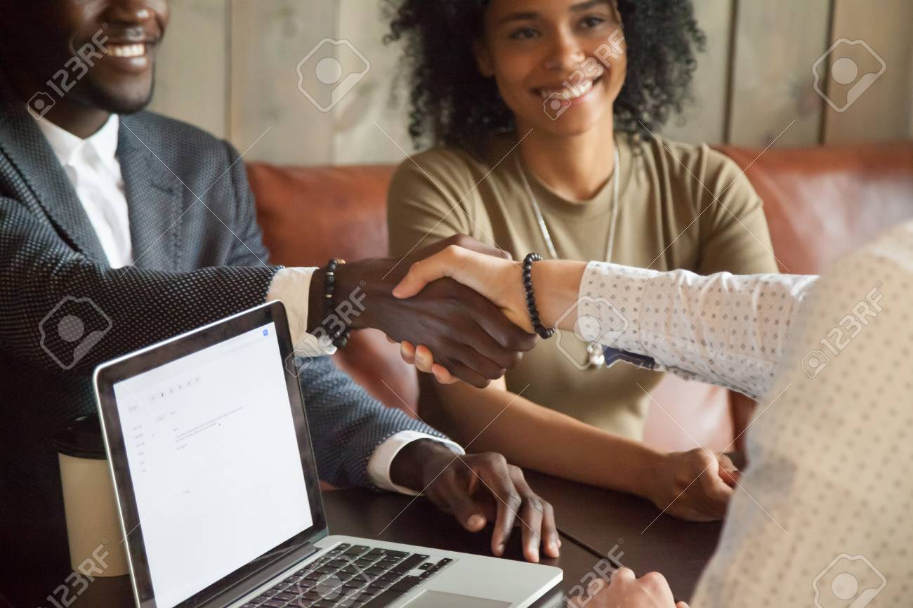Happy young african american couple making deal handshaking caucasian insurance broker in cafe, black satisfied customer and realtor or sales person shaking hands at meeting in office with laptop - 94746623