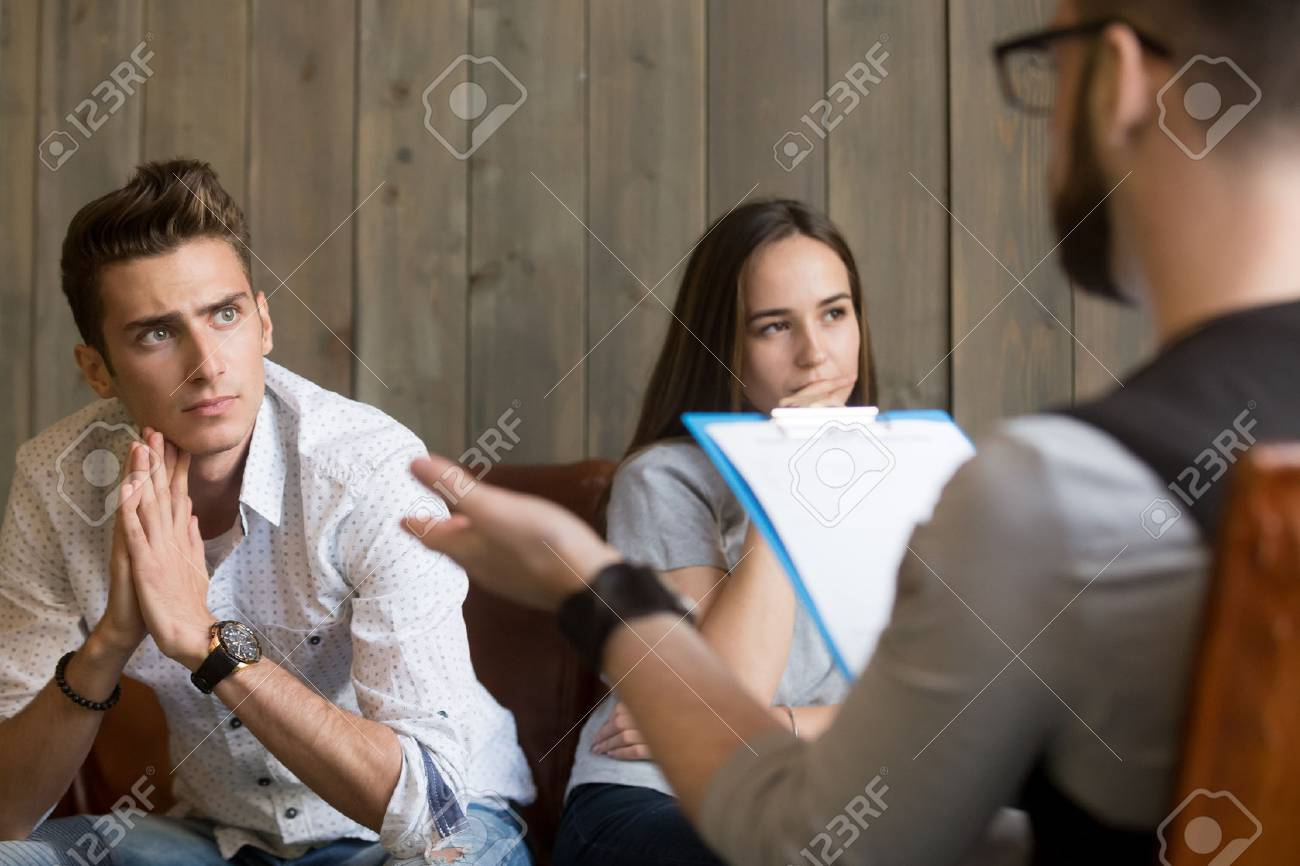 Frustrated young man listening to psychologist while his offended girlfriend sitting apart, family counselor talking to unhappy couple solving problems in relationships at counseling therapy session - 94768779