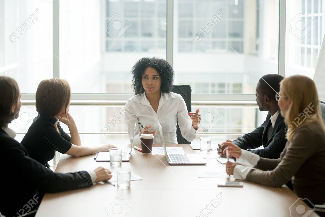 Black female boss leading corporate multiracial team meeting talking to diverse businesspeople, african american woman executive discussing project plan at group multi-ethnic briefing in boardroom - 97035374