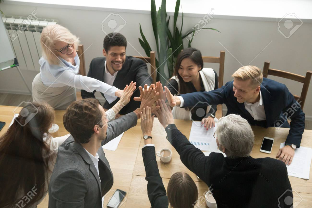 Diverse motivated multi-ethnic business team giving high five showing unity concept, young and old corporate group join hands promising support in collaboration, help commitment in teamwork, top view - 97384813