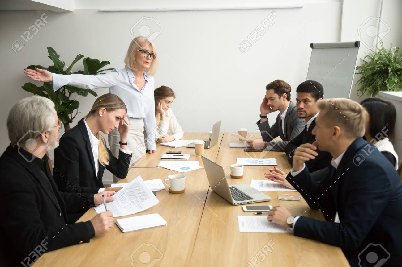 Angry senior woman boss firing unprofessional employee with hand gesture at diverse team meeting, dissatisfied aged female executive dismissing incompetent manager for bad work result in boardroom - 97384973