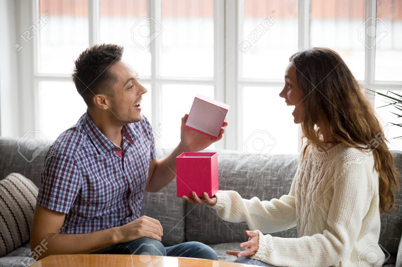 Excited Young Husband Opening Box Receiving Birthday Present From Wife Cheerful Happy Boyfriend Likes New
