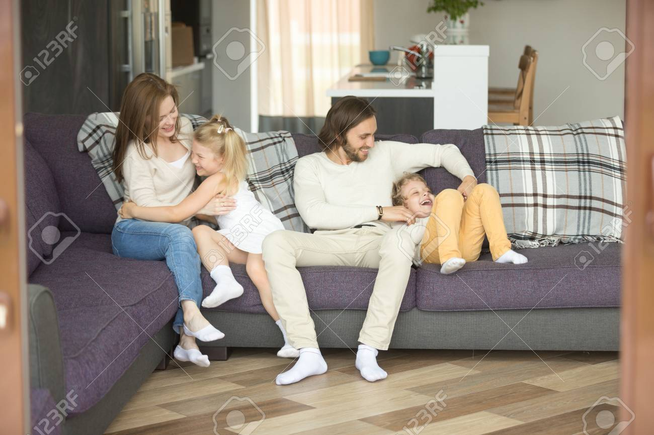 Cheerful Parents Playing With Kids On Sofa Laughing Together