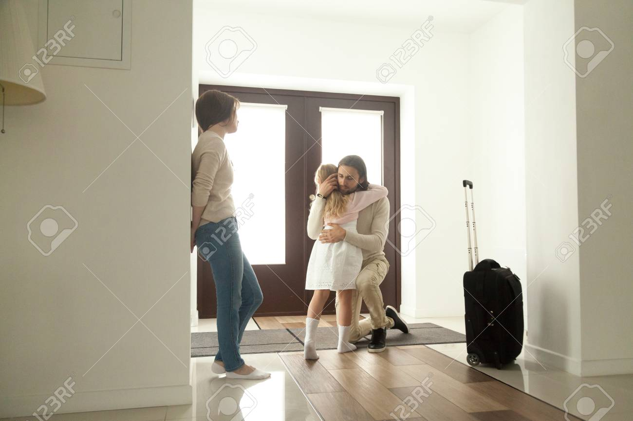 Little kid girl embracing dad leaving family moving out with travel case, sad daughter hugging father in house hall saying goodbye to daddy going away, unhappy child of divorced parents concept - 100266605