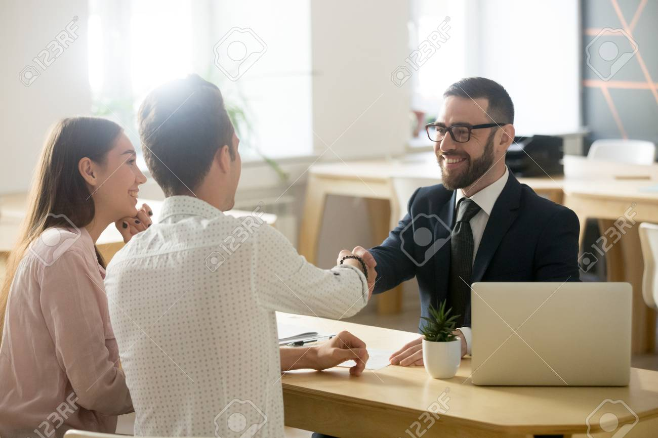 Smiling lawyer, realtor or financial advisor handshaking young couple thanking for advice, insurance broker or bank worker and millennial customers shake hands making deal, investment or taking loan - 100853706