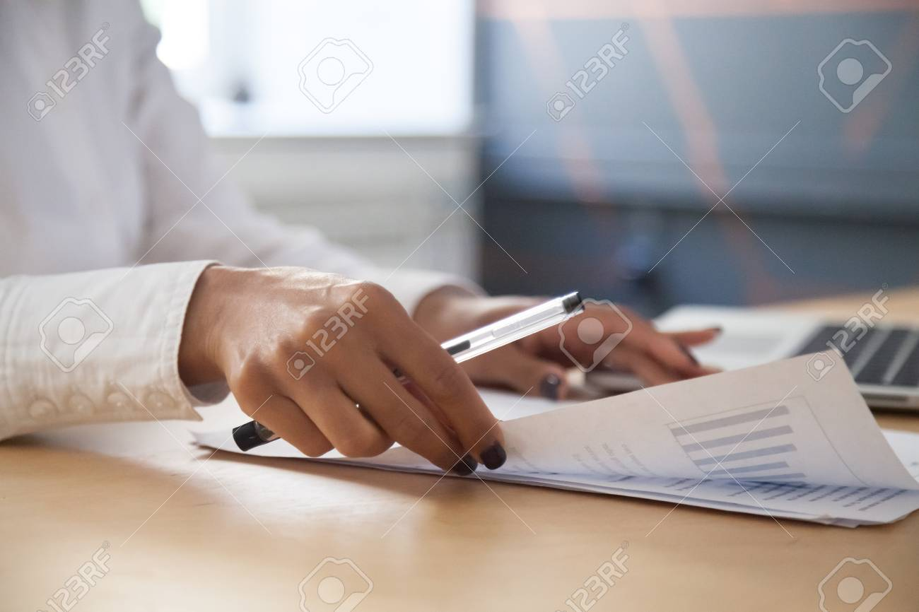 African american businesswoman analyzing project statistics result in report working with graphs documents and laptop in office, strategic planning and financial data analysis concept, close up view - 100856369