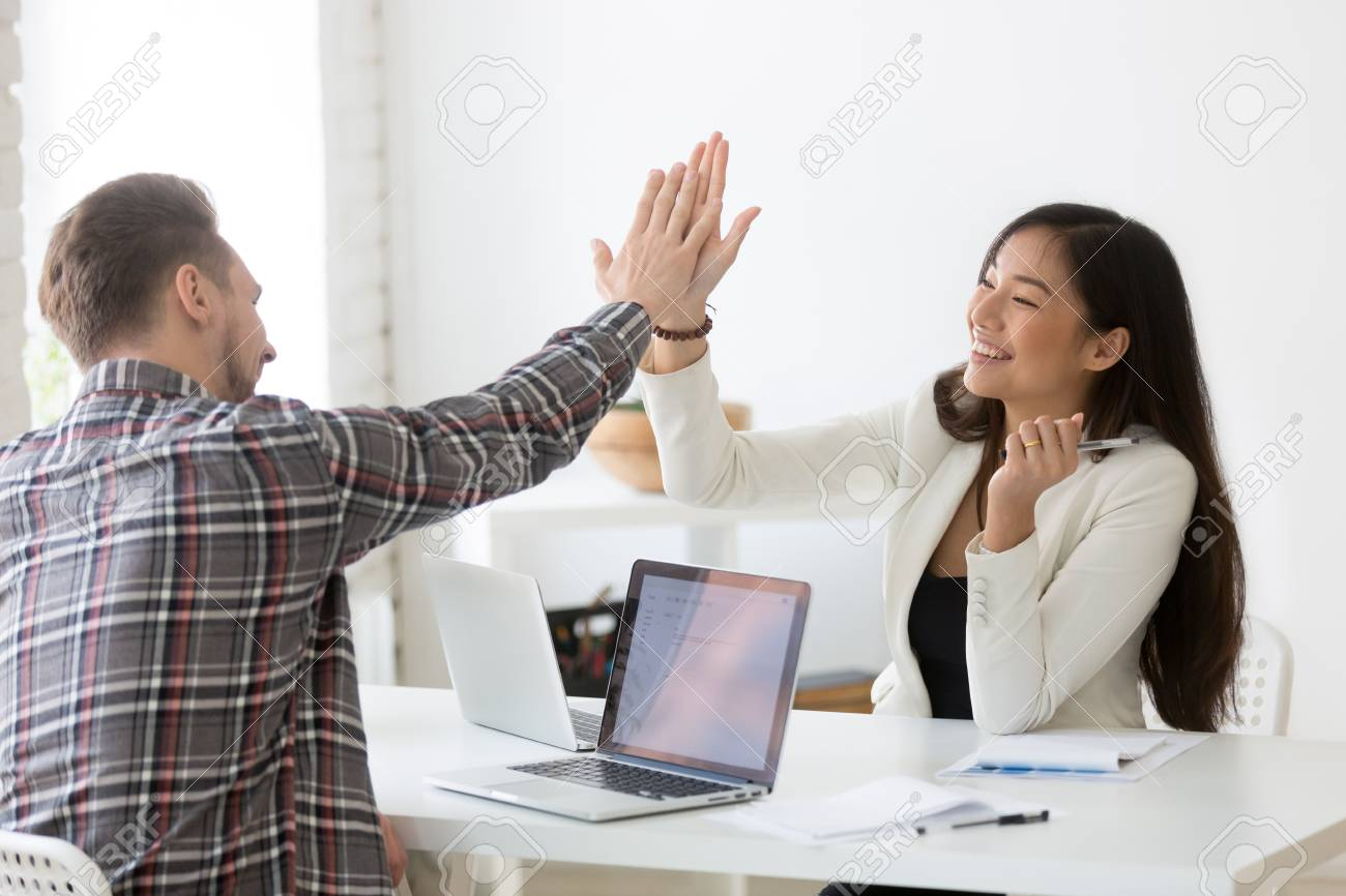 Young asian and caucasian partners giving high five at workplace, diverse motivated colleagues celebrate goal achievement - 101473378