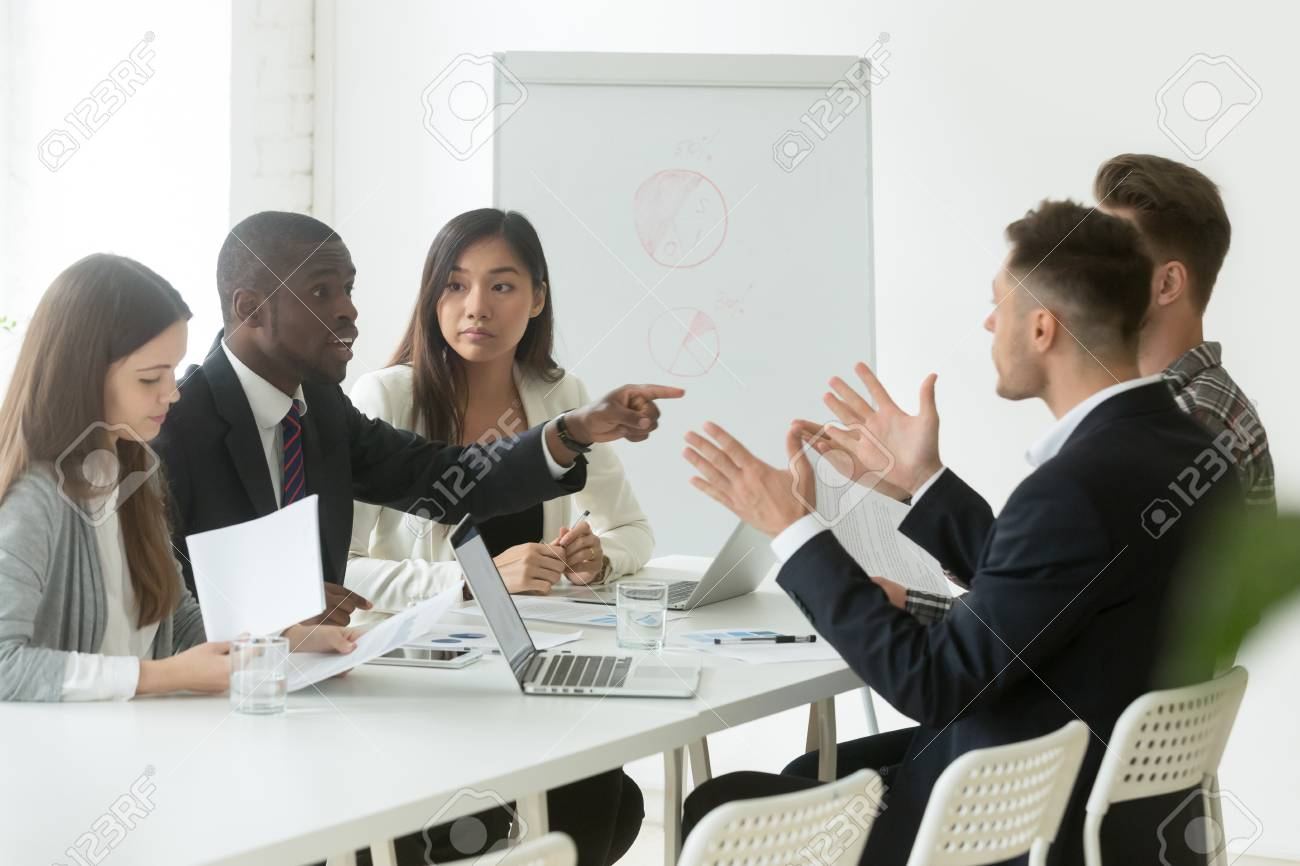 Diverse employees arguing during team meeting, african office worker disagreeing with caucasian colleague - 101473201