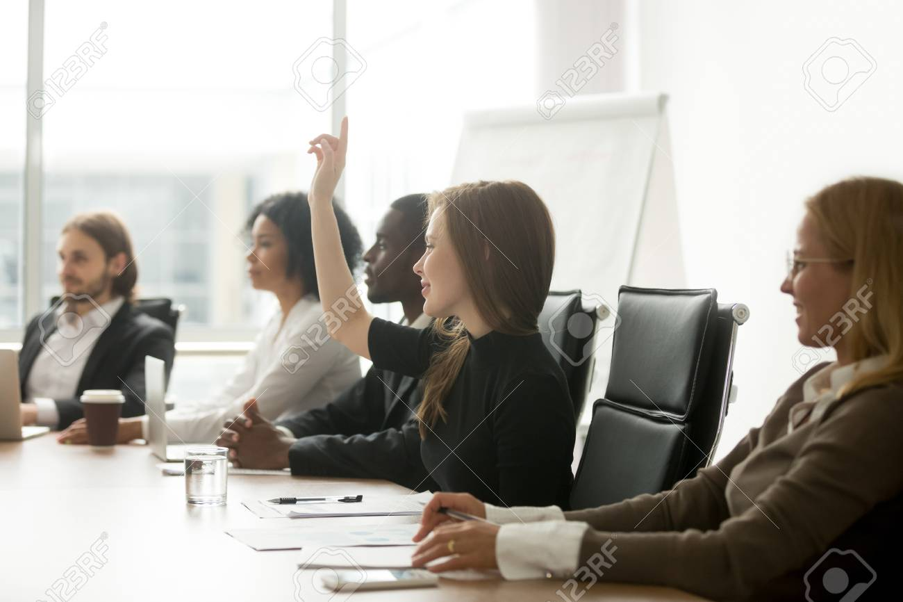 Smiling curious young businesswoman raising hand at multiracial group meeting engaging in offered activity - 101472825