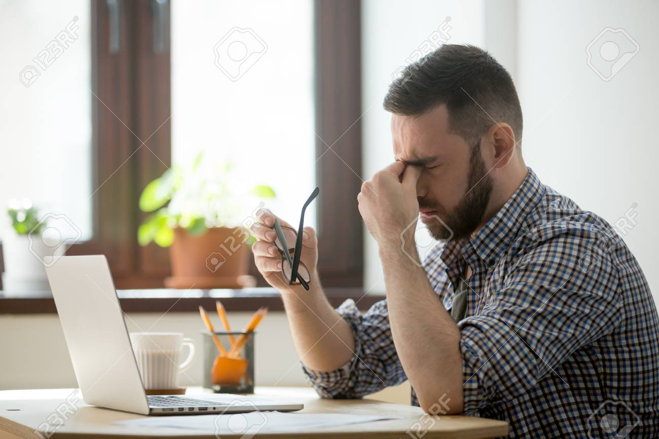 Tired stressed male worker taking off glasses, person massaging nose bridge suffering from headache and trying to relieve pain. Despaired man frustrated after reading company collapse or failure news - 101585245