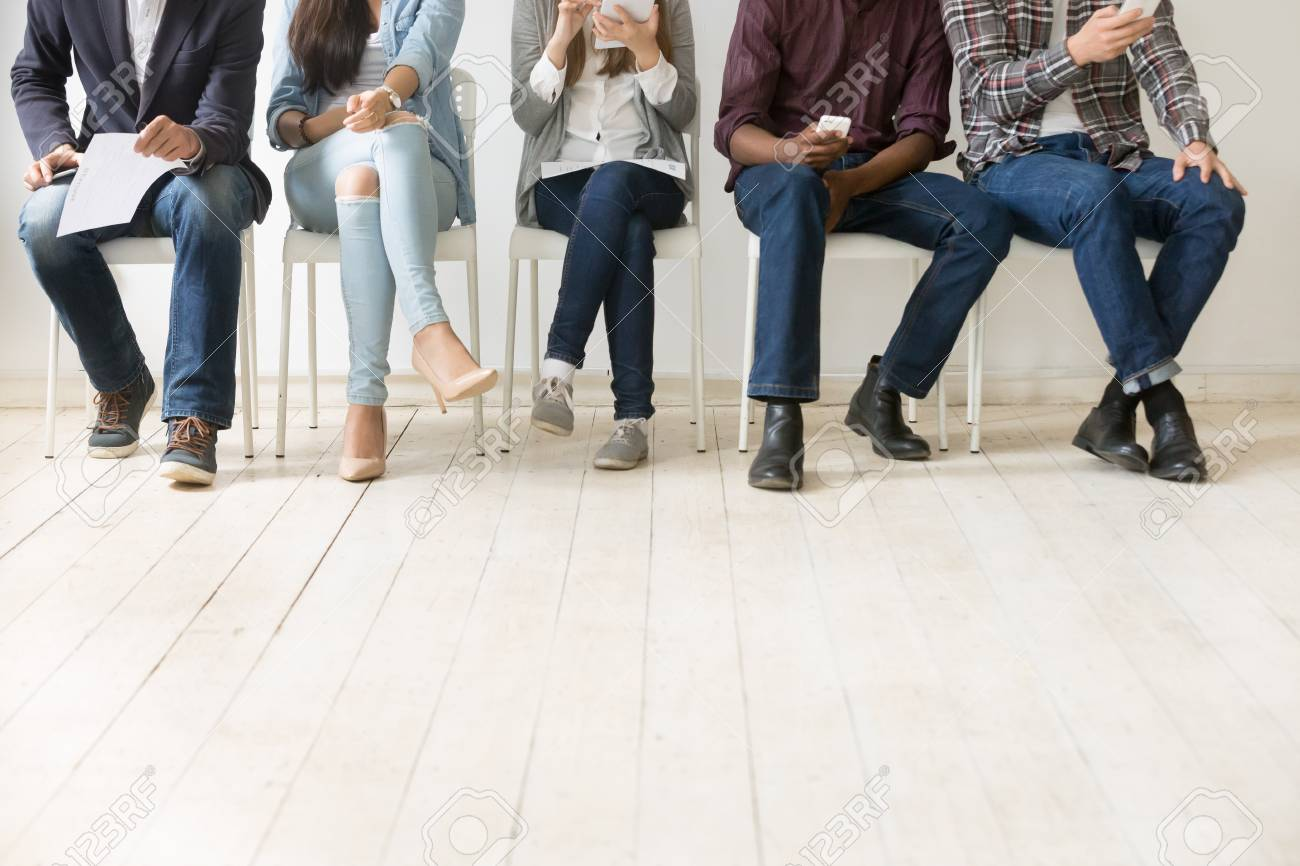Close up view of diverse work applicants sitting together, holding smartphones, tablets and papers getting ready for interview, multiethnic candidates waiting in queue. Employment, hiring concept - 103952211