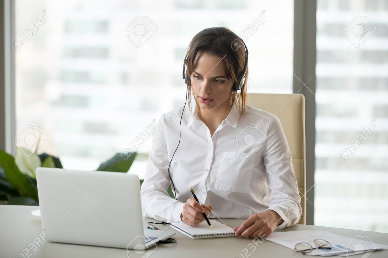 Serious businesswoman in headphones watching webinar on laptop making notes, learning studying computer course, making call, participating online conference, interpreter translating training class - 107344085