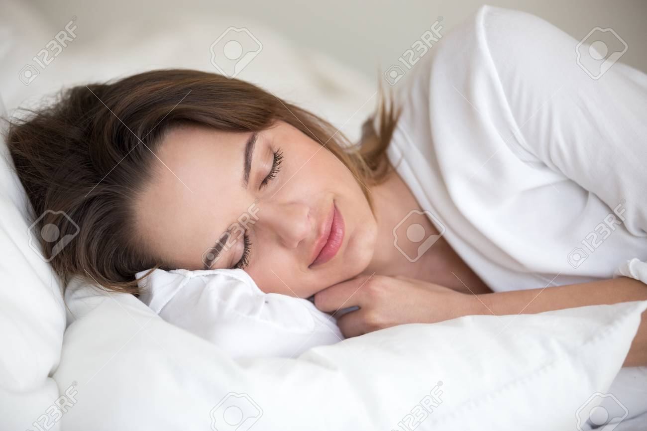 Young woman with beautiful face sleeping well on white cotton sheets and soft pillow lying asleep in comfortable cozy bed at home or hotel enjoying healthy nap resting enough for good relaxation. - 107344268