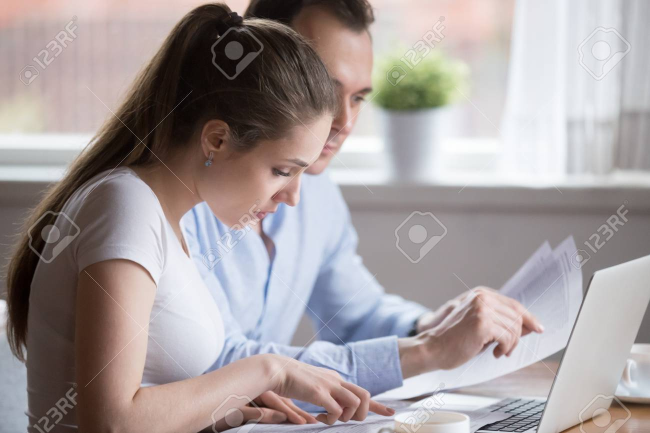 Serious millennial couple read documents managing house utility bills, man and woman analyze bank notice or insurance considering terms, husband and wife hold papers calculating finances or budget - 107686471