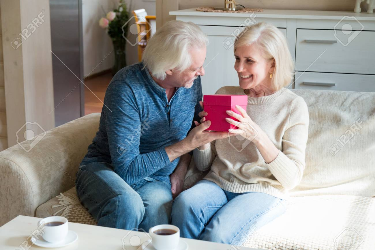 Loving Older Husband Presenting Romantic Birthday Gift To Mature Smiling Wife Caring Elderly Man Giving