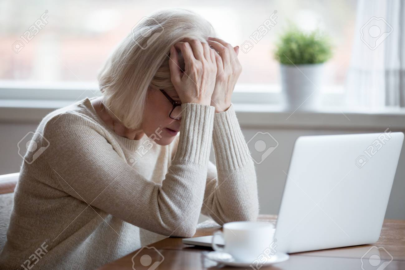 Upset depressed mature middle aged woman in panic holding head in hands in front of laptop frustrated by bad news, online problem or being fired by email feeling desperate shocked exhausted concept - 109260376
