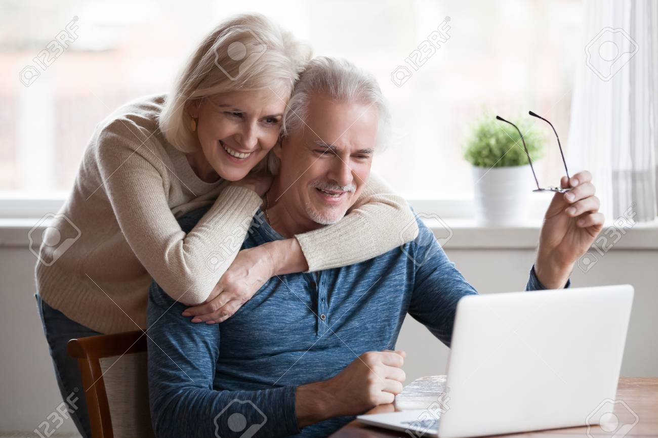 Senior middle aged happy couple embracing using laptop together, smiling elderly family reading news, shopping online at home, older people and computer or good vision after laser correction concept - 109260394
