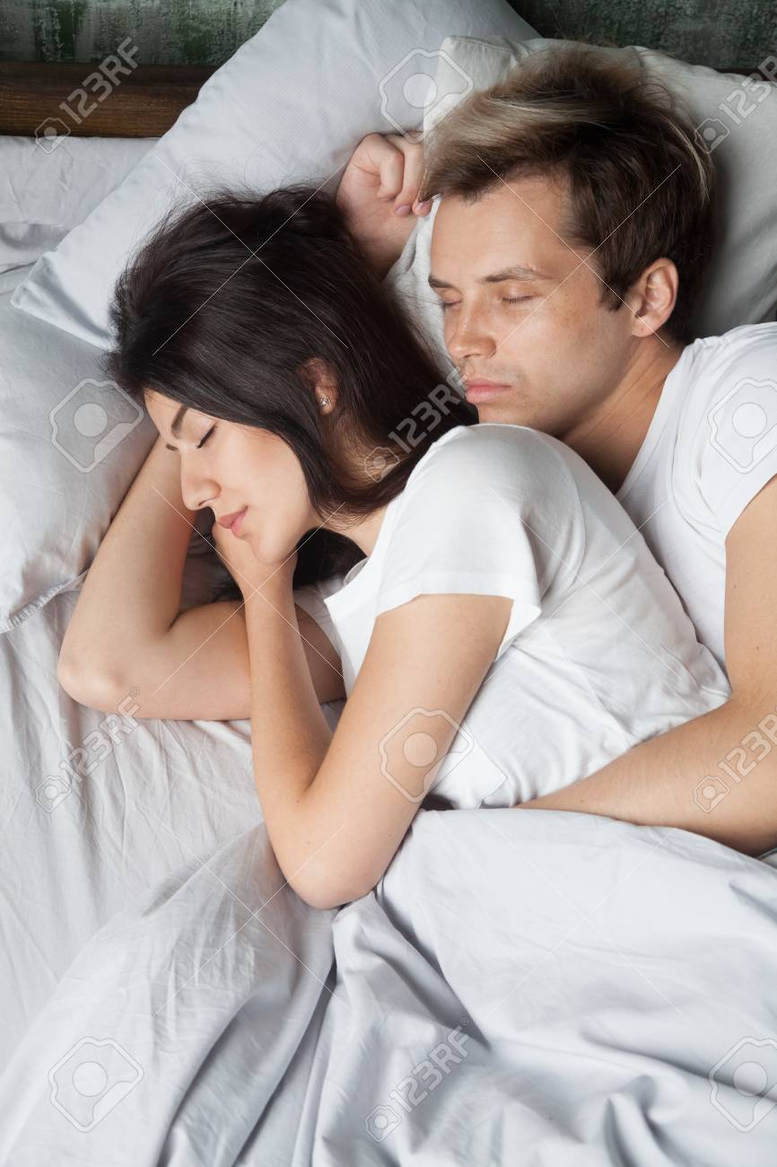 Young Male And Female In Love Sleeping And Embracing In Bed On ...