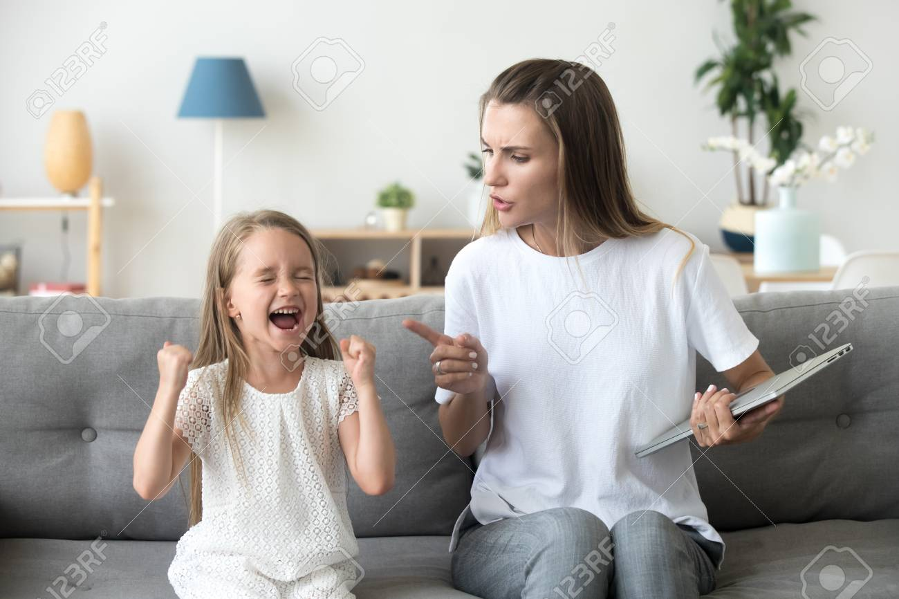 Stubborn little girl scream loud not listening to strict mom, serious young mother scold shouting daughter for bad behavior, working mommy lecture kid yelling asking attention. Family conflict concept - 110778578