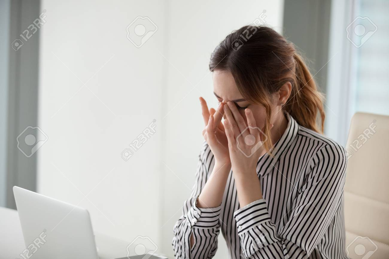 Tired young woman massaging nose bridge at workplace. Businesswoman experiences discomfort from long work at computer. Bad eye vision concept - 111159525