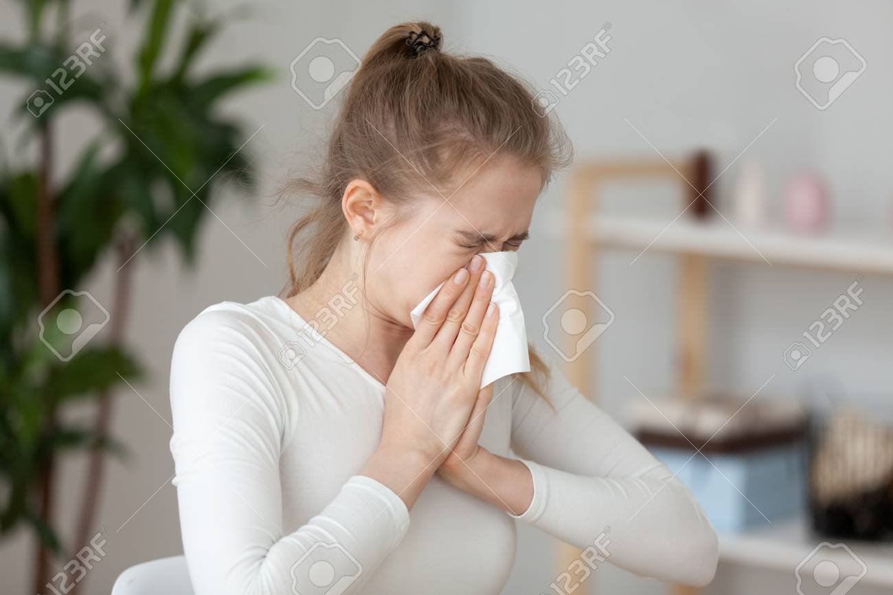 Young millennial sick woman sitting alone at work office sneeze holding tissue handkerchief and blowing wiping her running nose. Student girl has seasonal allergy or chronic sinusitis disease concept - 111159950