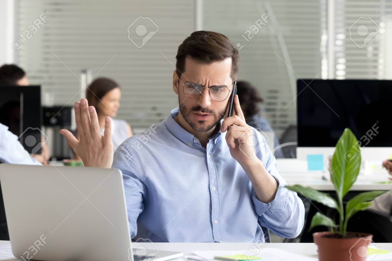 Angry business man talking on phone disputing looking at laptop, stressed frustrated office worker arguing by mobile solving online computer problem with technical support complaining on bad service - 111160771