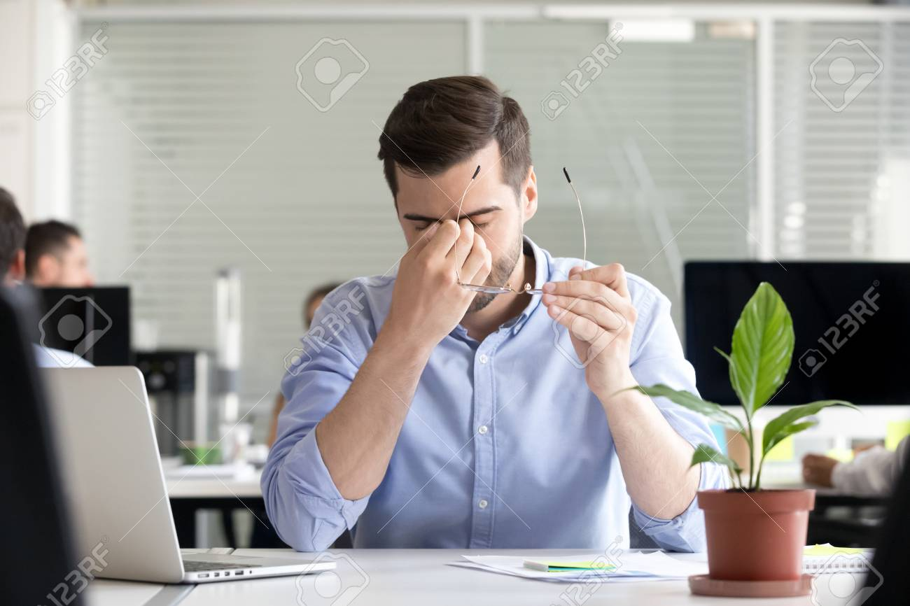 Tired businessman taking off glasses lost productivity after office work laptop use to relieve dry irritated eyes feeling fatigue tension or strain, chronic computer syndrome, bad weak vision problem - 111160799