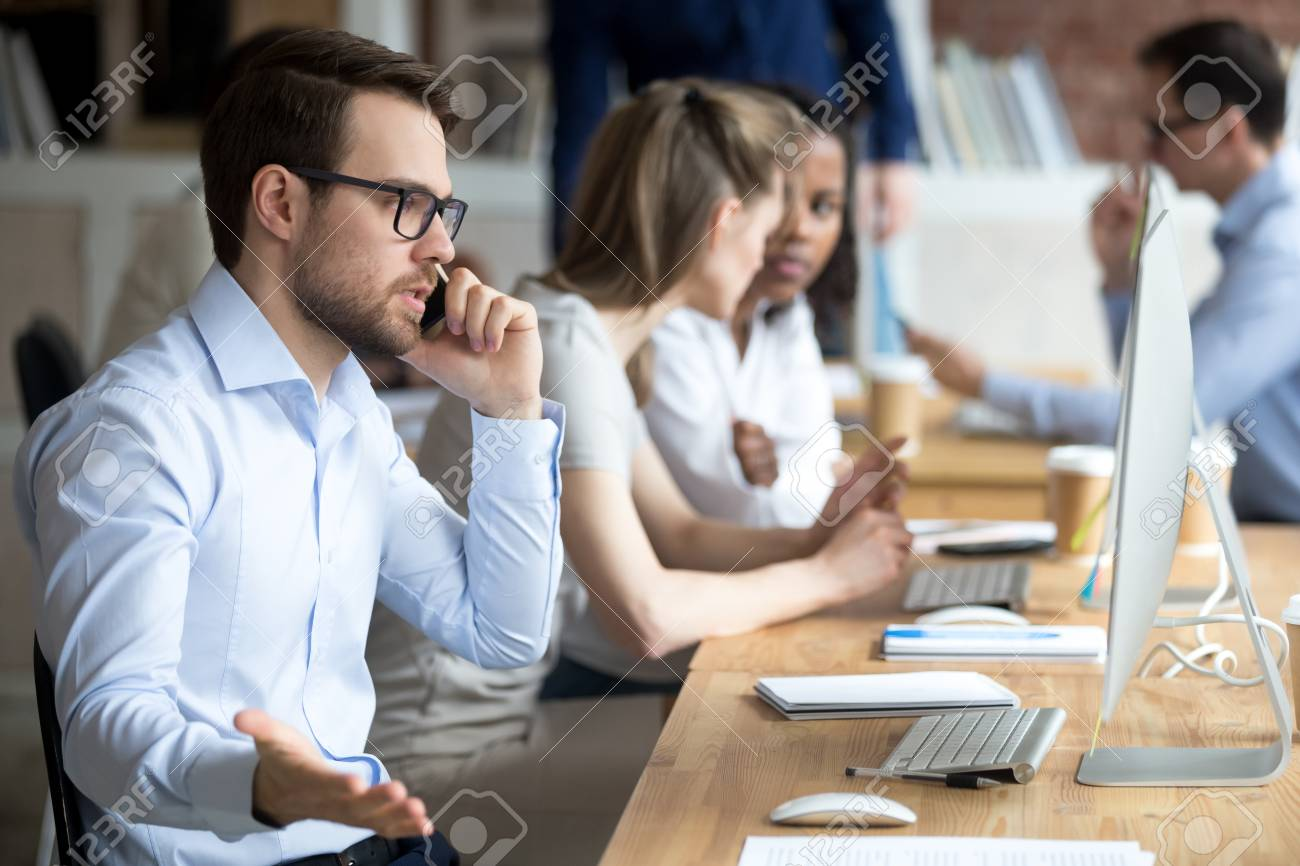 Angry male employee confused working at computer, solve business problems on phone, mad worker talk on cell arguing with client or customer, man busy at pc having serious conversation on cellphone - 112479827