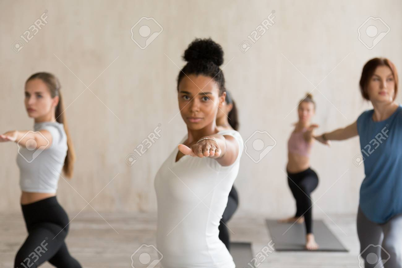 Black yogi woman and a group of young people practicing yoga