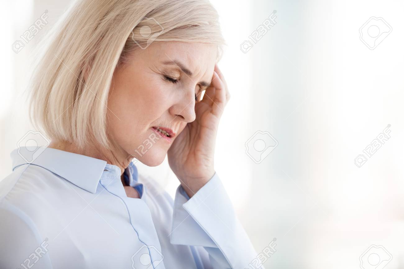 Tired upset mature old businesswoman suffering from strong chronic headache migraine or memory loss at work, stressed dizzy fatigued middle aged senior woman office worker feels pain in aching head - 112485485