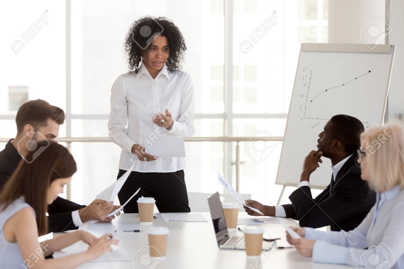 African american female project manager presenting report speaking at diverse group meeting, serious mixed race woman team leader talking to office workers explaining new business plan at briefing - 112485784