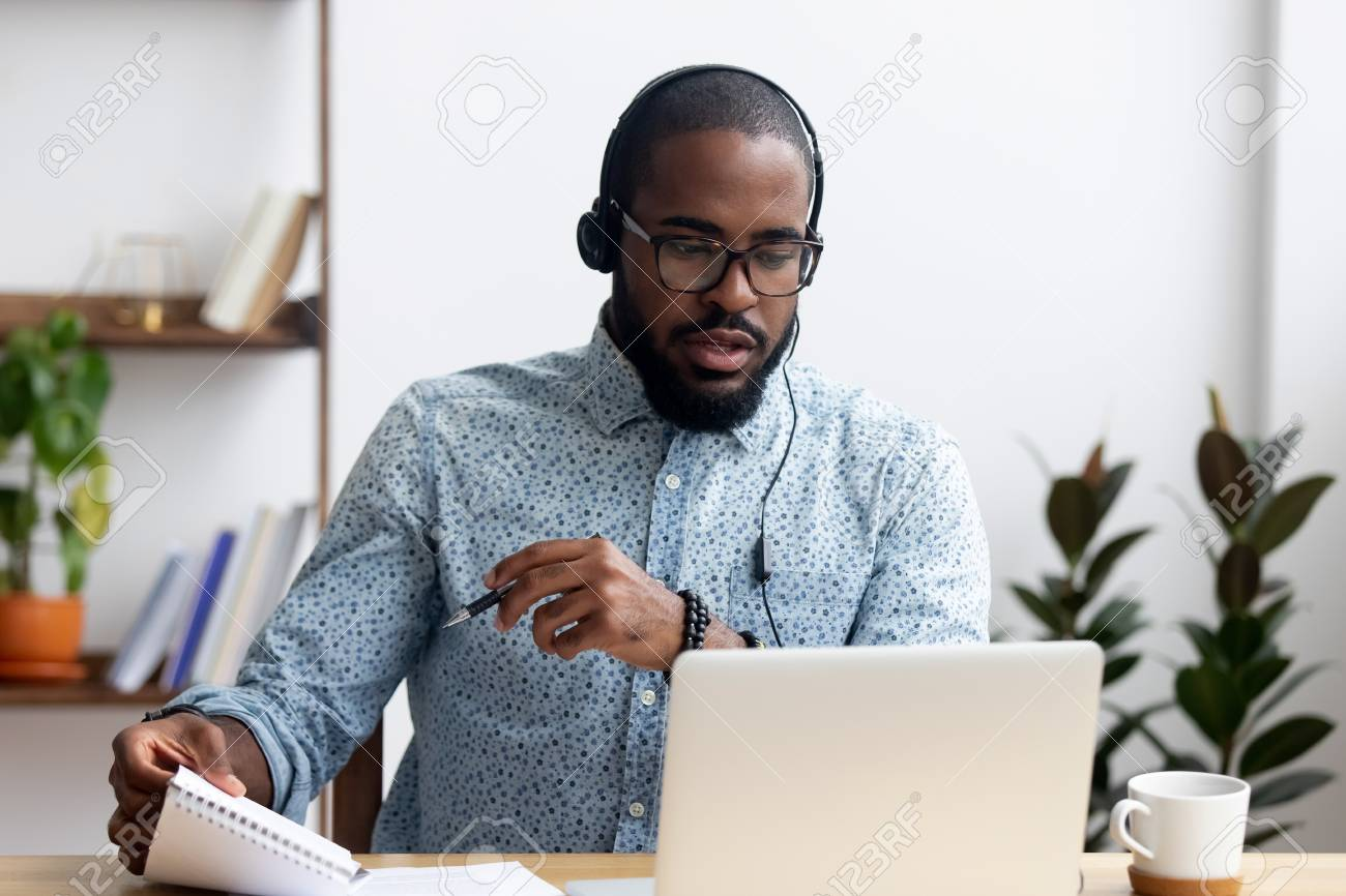 Black young man sitting at table wearing headphones learn foreign language improves knowledge looking at pc screen listening audio lesson holding pen and notepad makes some notes. E-learning concept - 114277925