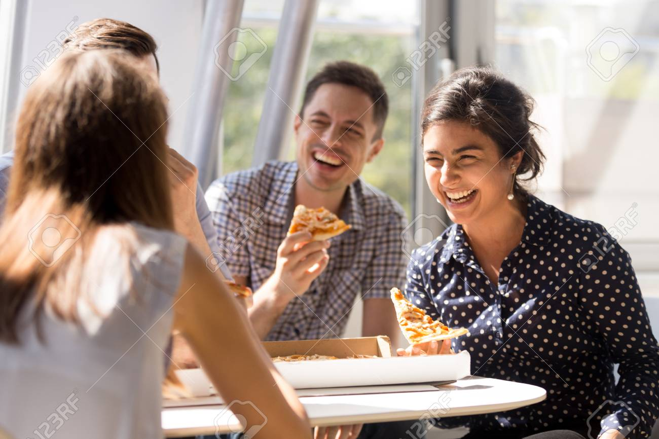 Indian excited woman laughing at funny joke, eating pizza with diverse colleagues in office, happy multi-ethnic employees having fun together during lunch, enjoying good conversation, emotions - 114277962