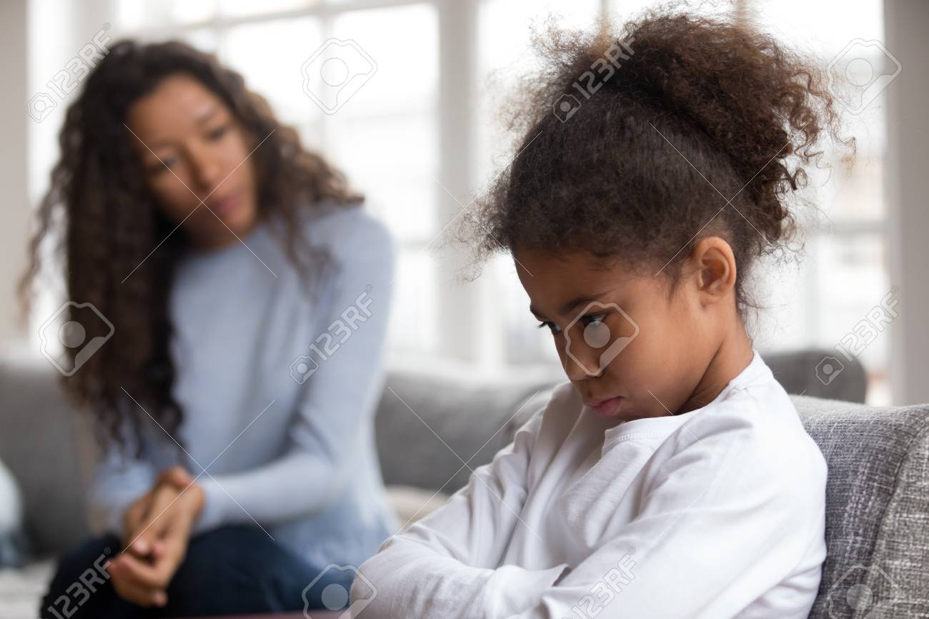 Mom or psychologist talking counseling upset offended african american child girl feels sad insulted, sulky frustrated black mixed race kid daughter having psychological trauma depression problem - 115422721