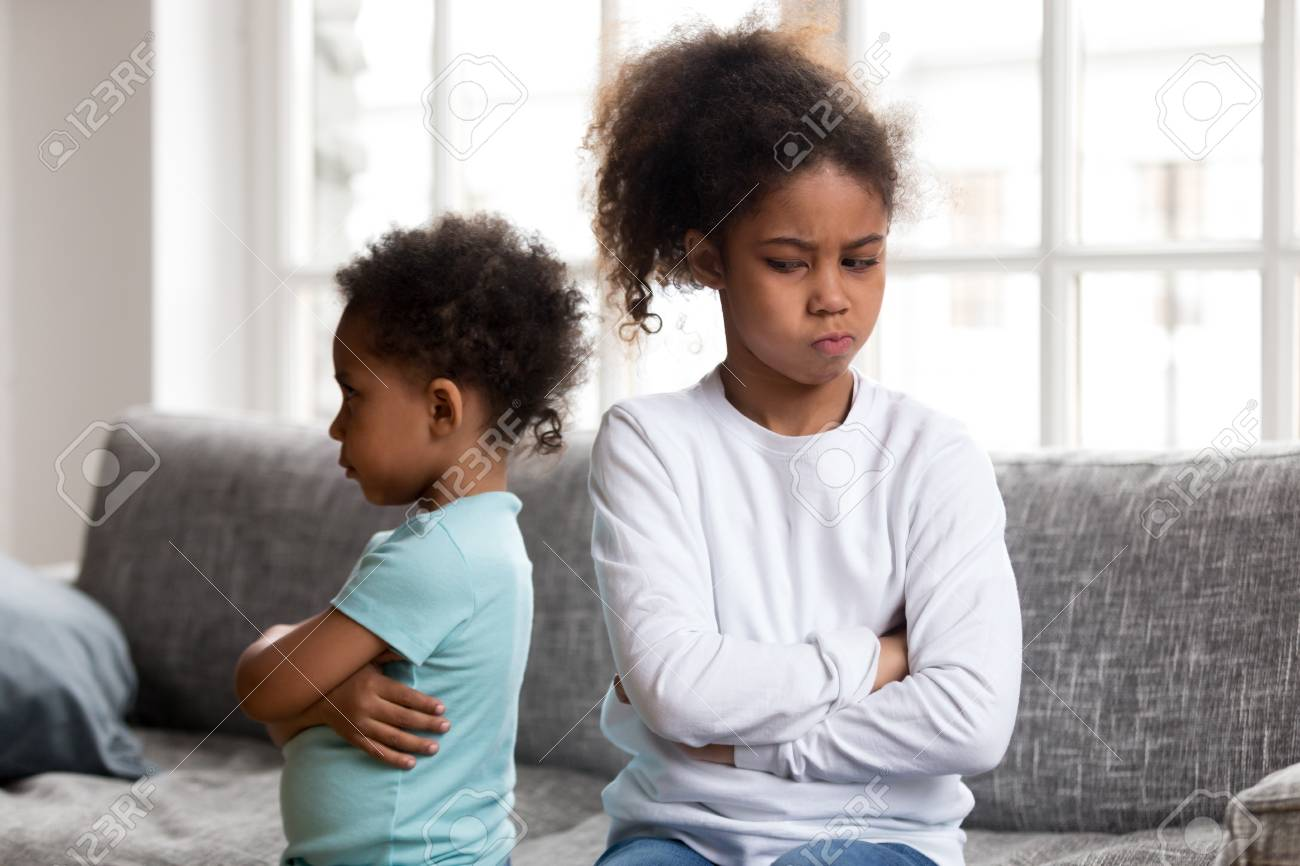Angry stubborn african preschool girl sister and offended little boy brother ignoring each other sitting on couch feel jealous avoiding talk, 2 children conflict, siblings rivalry bad relationship - 115425428