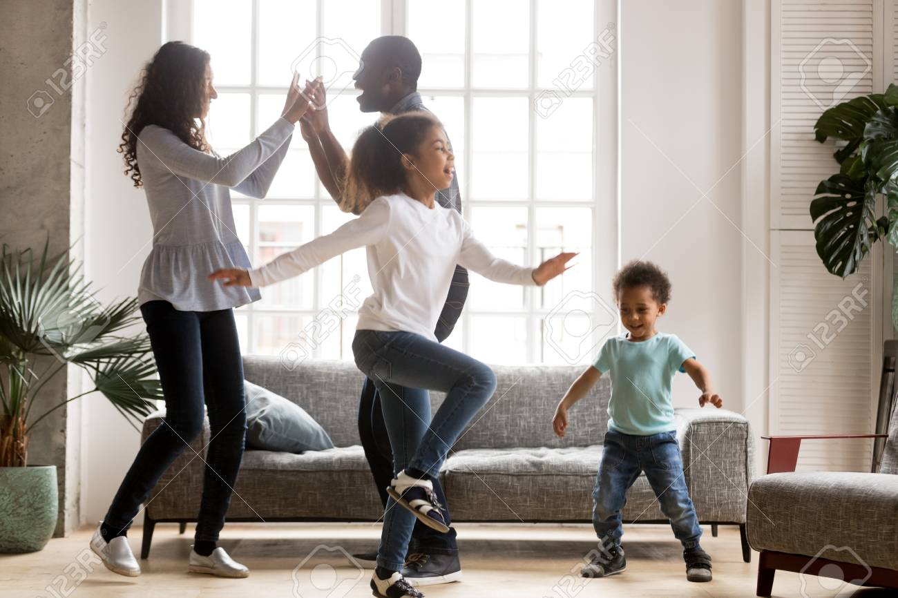 Happy african american family and funny active children having fun dancing together at new home, cheerful black parents and two kids enjoying moving to music spending weekend time in living room - 115425430