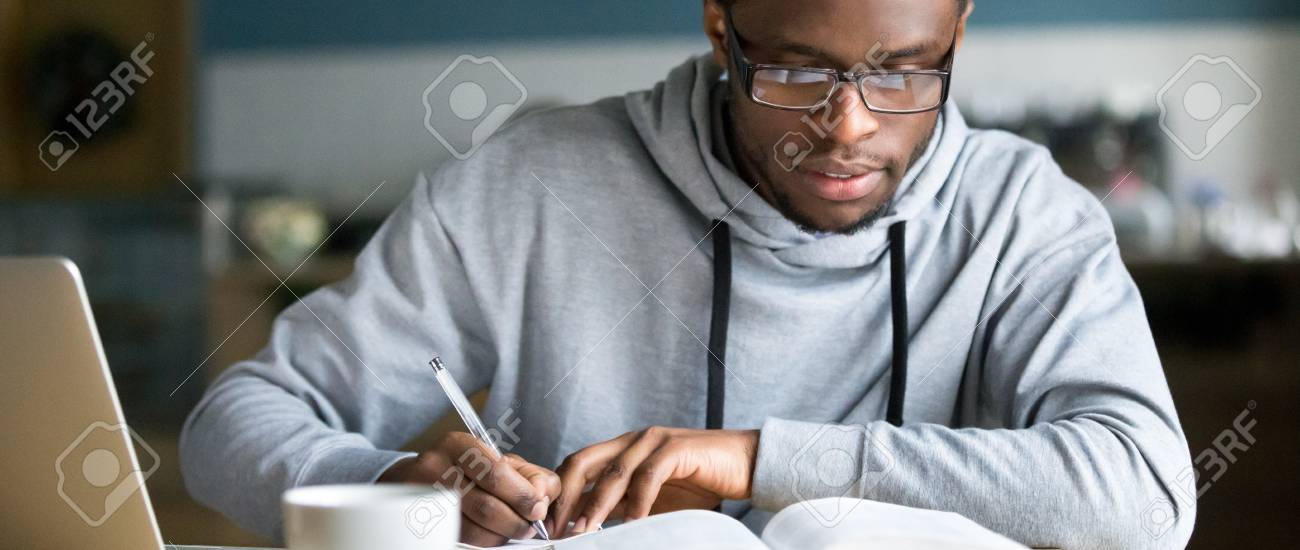 Closeup smart millennial african student wear glasses hold pen noting writing down information study use book preparing for university or college test exam, horizontal photo banner for website header - 116455929