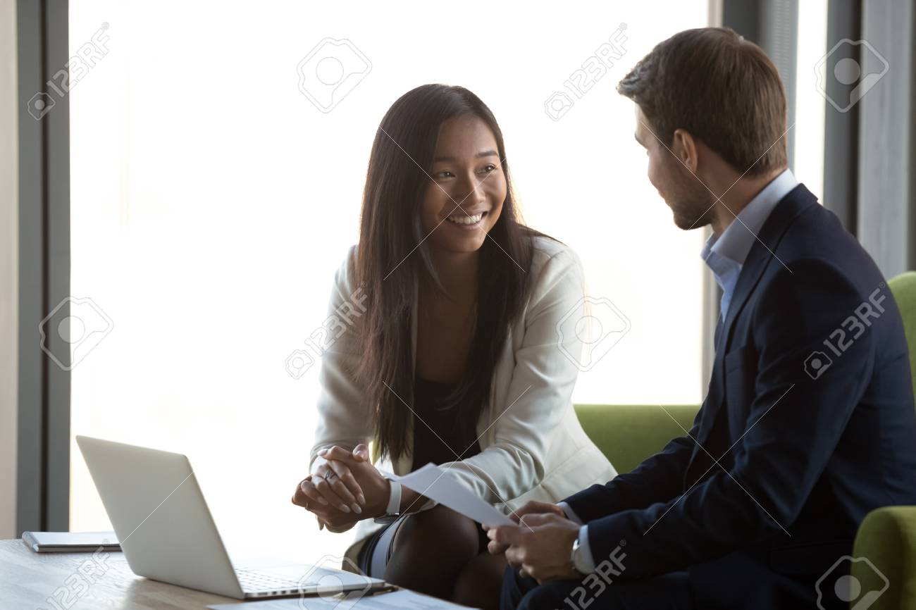 Friendly nice asian manager insurer hr smiling talking to candidate at job interview or business meeting promising contract benefits, happy diverse financial advisor and client having conversation - 116422295