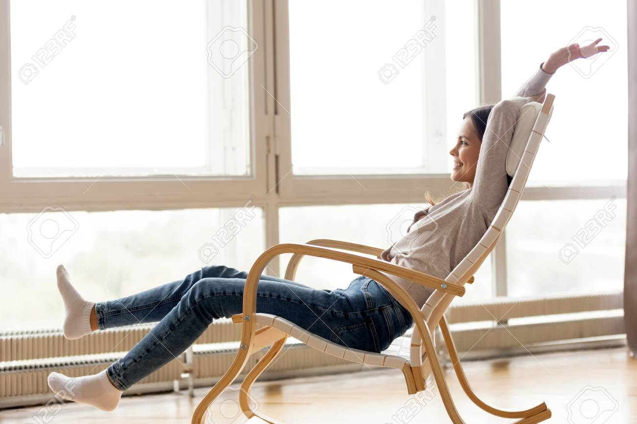 Astonishing Carefree Young Woman Relaxing On Comfortable Wooden Rocking Chair Download Free Architecture Designs Estepponolmadebymaigaardcom