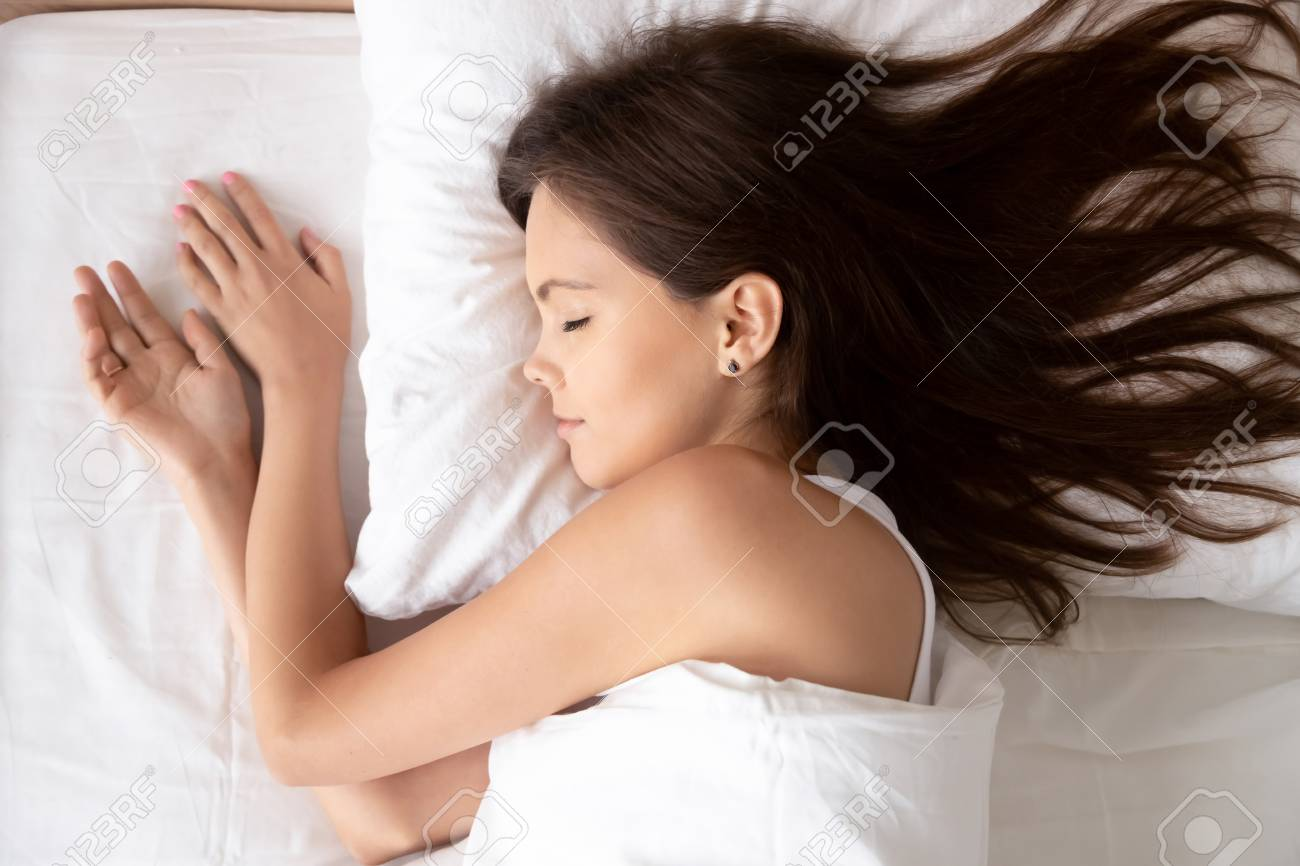 Young calm woman sleeping well in cozy comfortable bed lying on soft pillow orthopedic mattress, serene millennial girl resting enough in good healthy sleep nap on white cotton fresh sheets, top view - 116422365