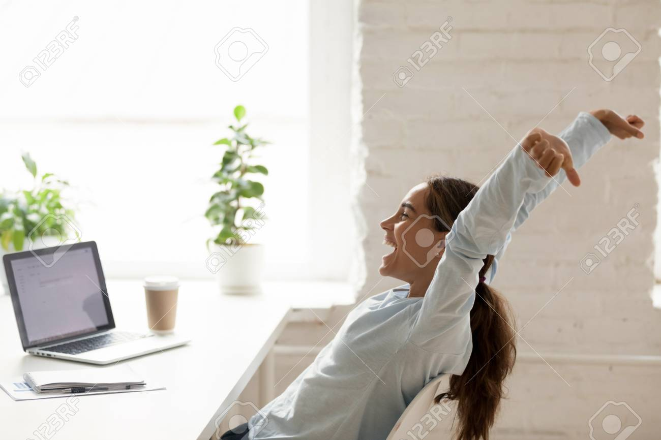 Cheerful mixed race woman sitting at workplace on chair bending stretching raising hands up, feels happy got a long-awaited post winning online lottery or accomplishing working day before vacation - 117288603