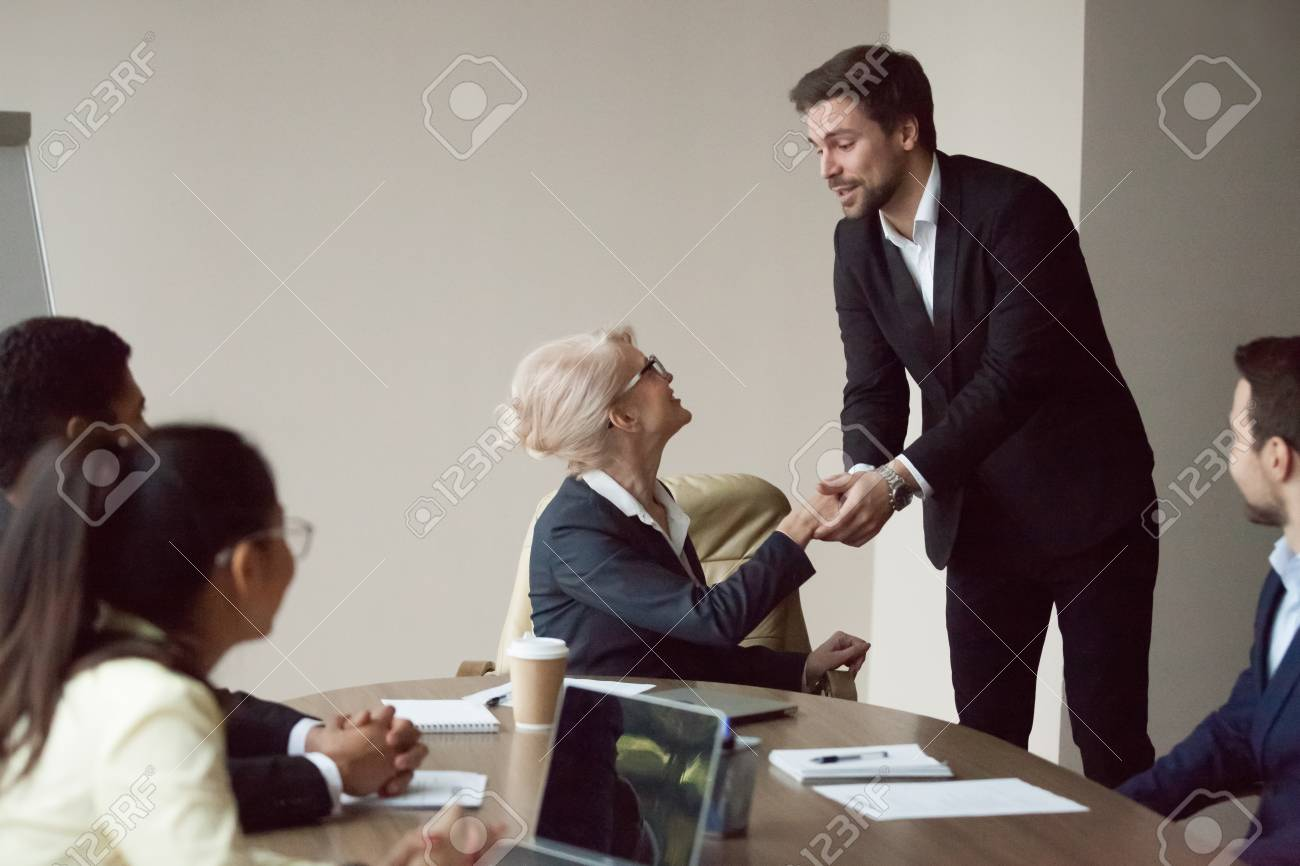 Satisfied grateful partner employee holding shaking hand of executive thanking for help or opportunity, expressing respect and gratitude at team meeting, making feedback compliments flattering boss - 117289103