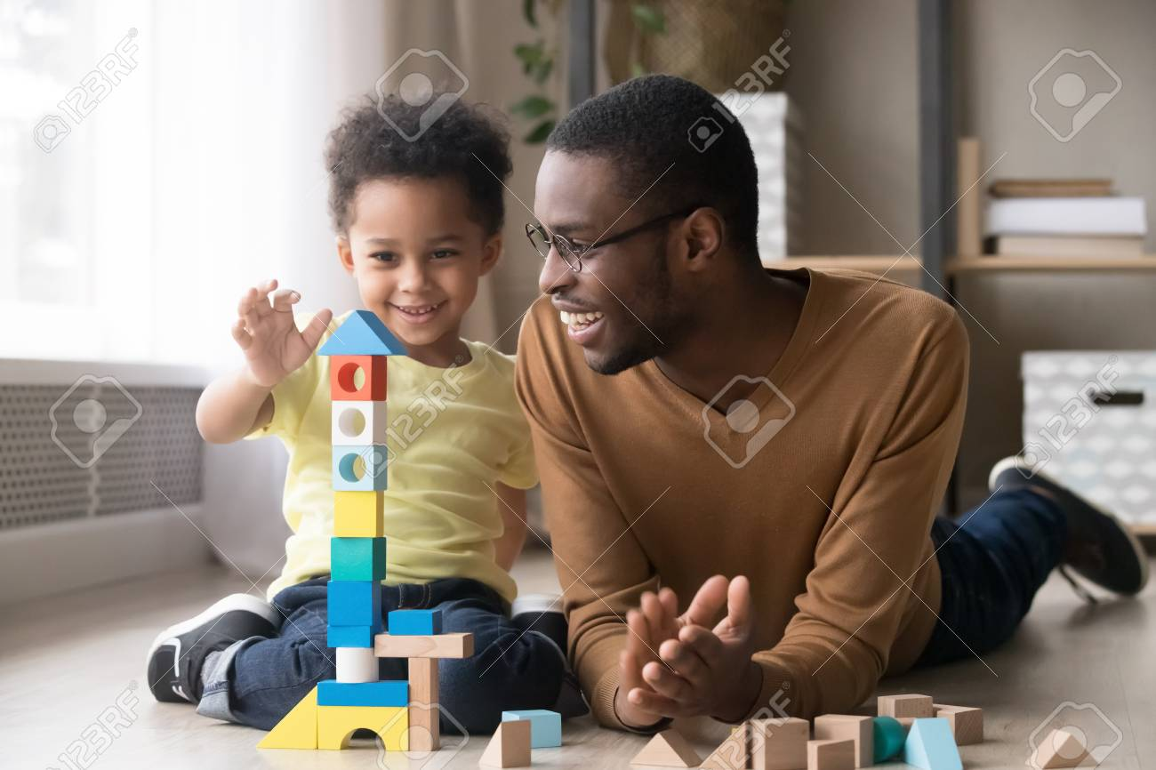 Happy cute little son playing game with black dad baby sitter building constructor tower from multicolored wooden blocks, african family father and toddler child boy having fun on warm floor at home - 117788456