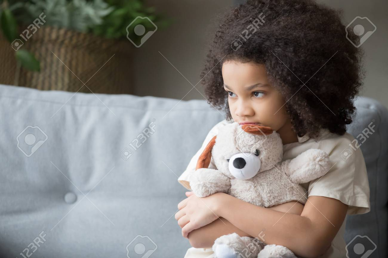 Upset lonely bullied little african american kid girl holding teddy bear looking away feels abandoned abused, sad alone preschool mixed race child orphan hugging stuffed toy, charity adoption concept - 117788458